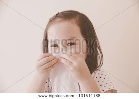 a girl cleaning nose with tissue wipesoft selective focus toning