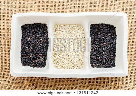 Sesame seeds in white bowl on sack background
