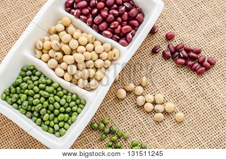 Mix of seeds beans green bean azuki or red bean soy bean on in white bowl on sack background.