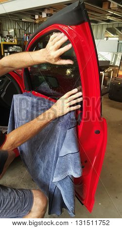 worker doing window tint on a red car