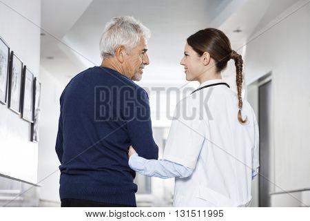 Female Doctor Holding Senior Man's Arm In Rehab Center