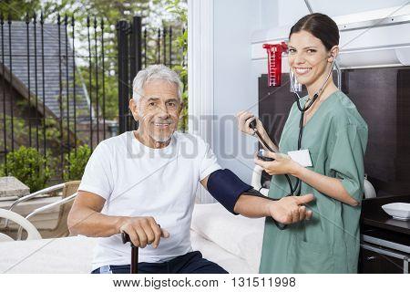 Senior Man's Blood Pressure Being Checked By Female Nurse