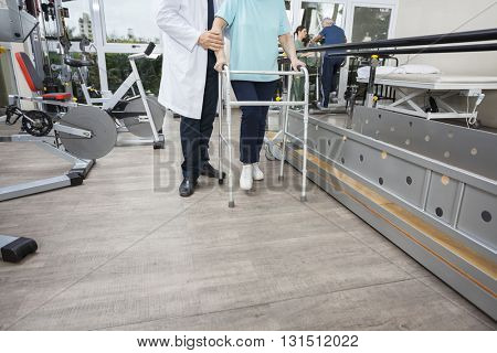 Low Section Of Physiotherapist Assisting Woman With Walker