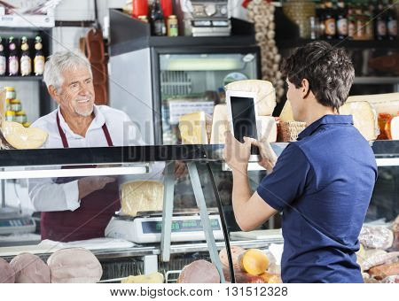 Man Photographing Salesman Packing Cheese In Shop