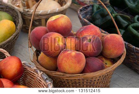 Peaches in wicker basket on farmers market table.