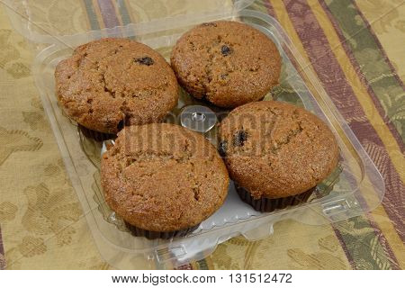 Plastic package of raisin bran muffins on table with tablecloth
