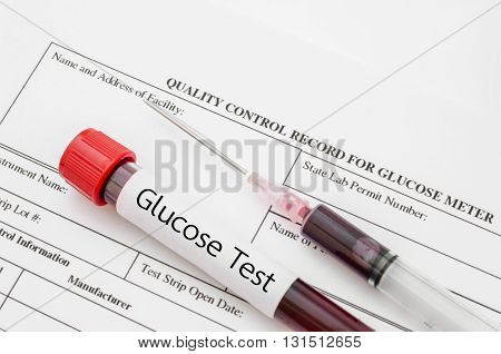 Sample blood for screening diabetic test in blood tube on blood sugar control record.