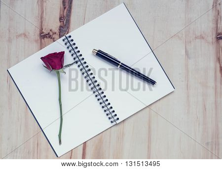 Notebook and pen with rose flower on wood background