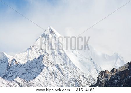 Mountain peak with snow in mist Yading national level reserve Daocheng Sichuan Province China