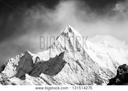 Mountain peak in monotone with snow cover there is clouds in background.