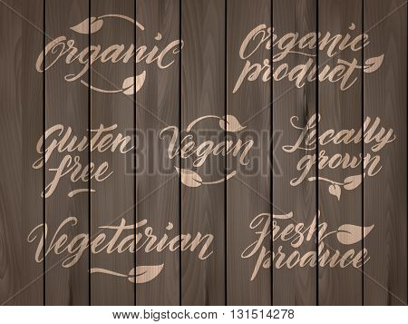 Retro styled healthy food letterings. Label, logo template stylized with stamp effect on a wooden background. Organic, organic product, gluten free, vegan, locally grown, vegetarian, fresh produce. Eps 10 vector. Wooden effect can be easily removed from l