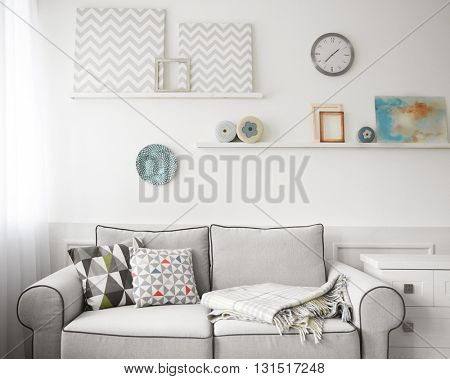 Living room interior, grey couch and shelves with paintings on wall background