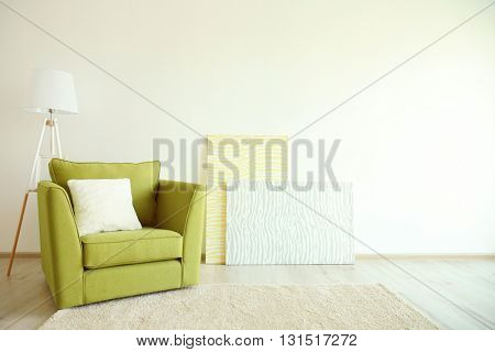 Green armchair and lamp on light wall background