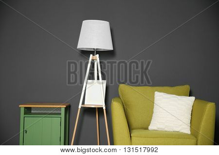 Room interior with green armchair on dark grey wall background