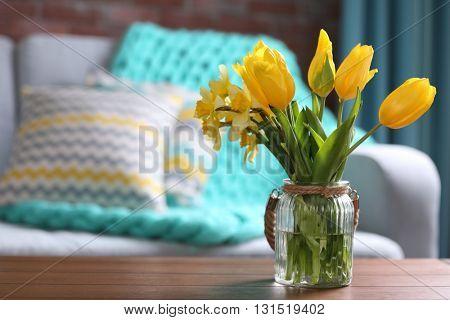 Yellow spring flowers in living room interior