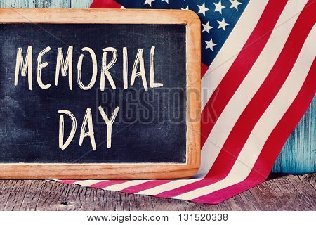 the text memorial day written in a chalkboard and a flag of the United States, on a rustic wooden background