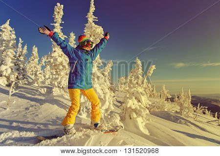 Snowboarder on a mountain with her hands raised