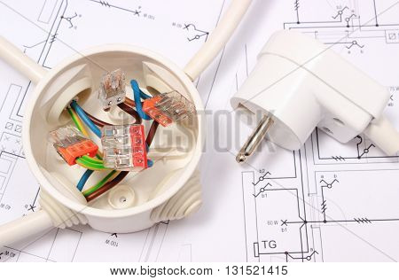 Copper wire connections in electrical box and electric plug lying on construction drawing of house accessories for engineering work energy concept