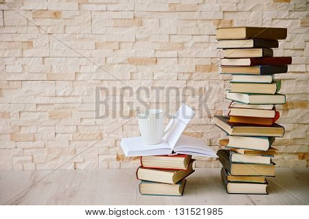 Pile of books on brick wall background