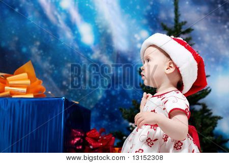 Christmas child standing in snowdrift against night stellar sky.