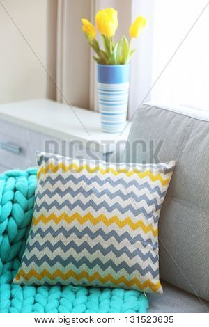 Stylish pillow on grey couch in room interior