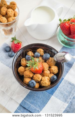 cereal flakes with fresh berries and milk for breakfast