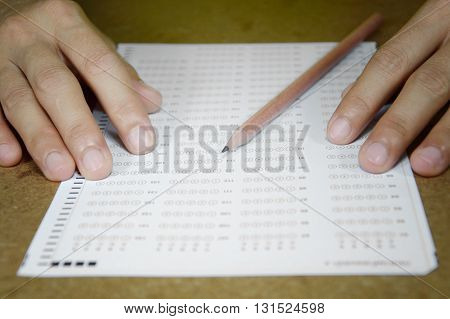 student filling answers sheet with a pencil
