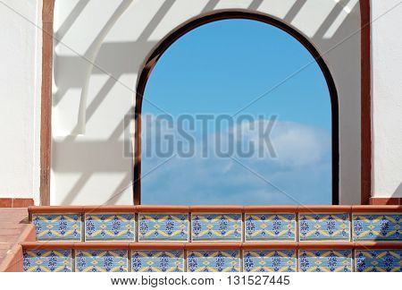 Sky view through archway and azulejos decorated stairs