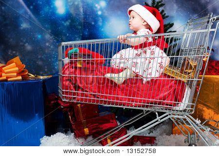 Christmas child sitting in a supermarket trolley against night stellar sky.