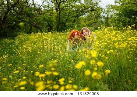 Best friends forever. Girlfriends are hiding in the flowers in the park. BFF. Close friends. Gentle friendship.