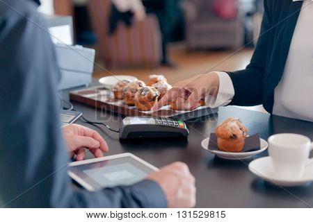 Making contactless payment over cafe counter with muffin humanhand with mobile phone with mobile phone held close to card reader