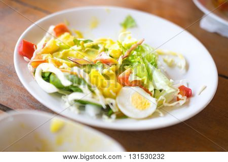 Eating vegetable saalad with boiled eggs on table