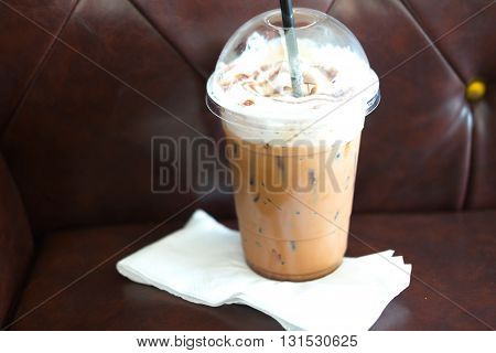 Iced mocha coffee in takeaway cup on sofa