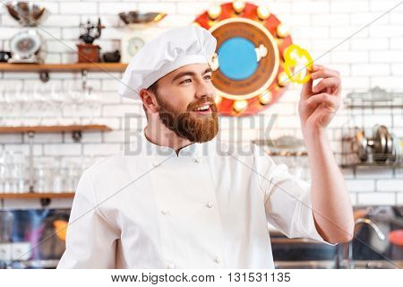 Smiling attractive cook cheif holding slice of yellow bell pepper  on the kitchen