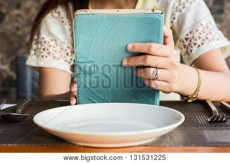 The Women Play The Mobile Phone Or Tablet While Waiting For The Food