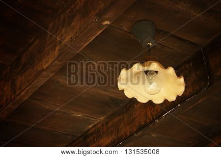 Antique Metal Light Hanging From Old Wooden Barn Ceiling