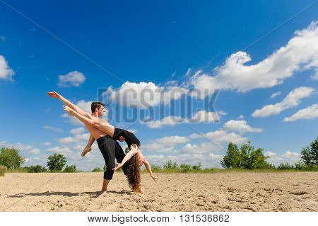Contemporary dance. Man and woman in passionate dance pose on beach. Young couple dancing modern dance in beautiful pose outdoors. Girl in jump against the sky clouds. A man with naked torso on sand.