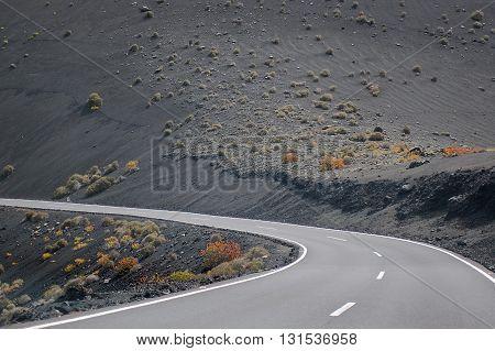 Asphalt road curve in volcanic mountain landscape