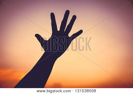 Silhouette Of A Hand On Colorful Sunset Sky Background.