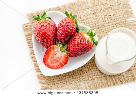 Strawberries in heart bowl shape with milk in glass.