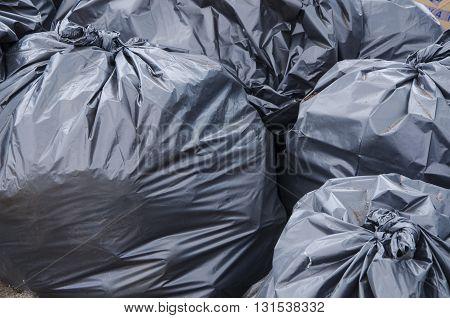 Set of big black bags of garbage on the floor
