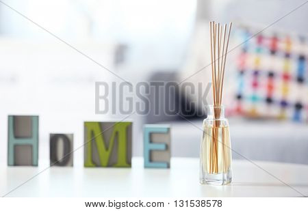 Handmade reed freshener with home word on white table in living room, close up