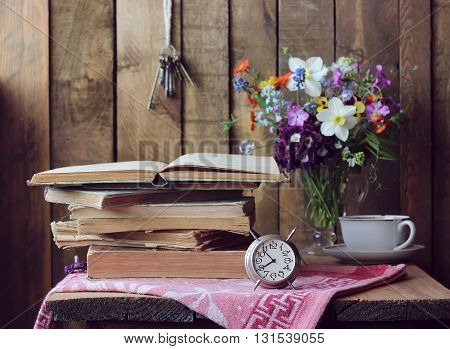 Retro still life with books alarm clock and a bouquet in the background in rustic style.