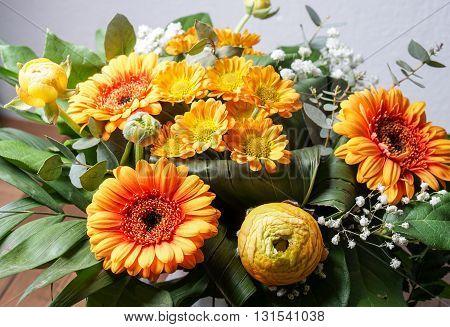 bouquet of orange flowers. Peonies Bridal Veils green leaves and daisies