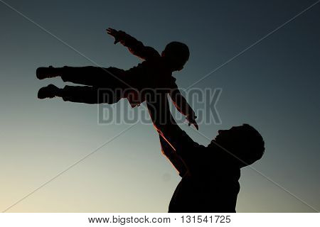 a father and son silhouette on sunset