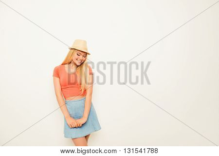 Shy Smiling Young Girl Posing In Skirt And Hat