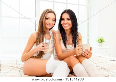 Two Pretty Sisters Laughing In Bedroom And Drinking Coffee