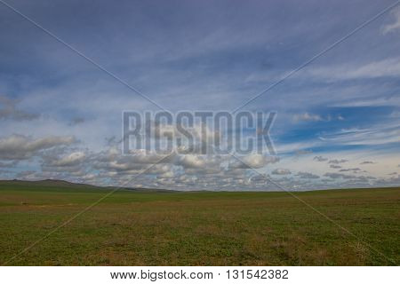 green field and blues sky with clouds - near Almaty Kazakhstan steppe 2016