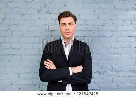 Portrait Of Serious Man With Crossed Hands On The Background Of Wall