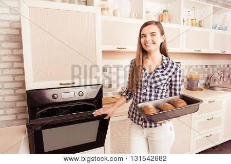 Pretty Young Woman Taking An Oven-tray With Baked Bread From Oven